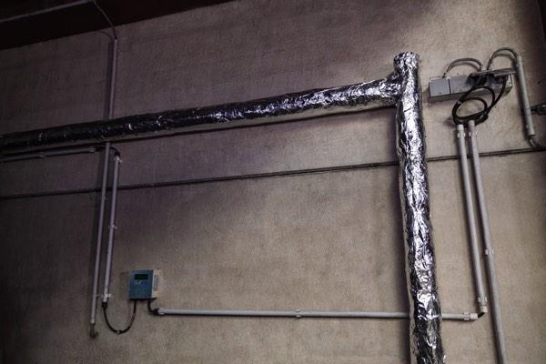 Leidingisolatie in een bedrijfsgebouw met minerale wol door Isolteam
